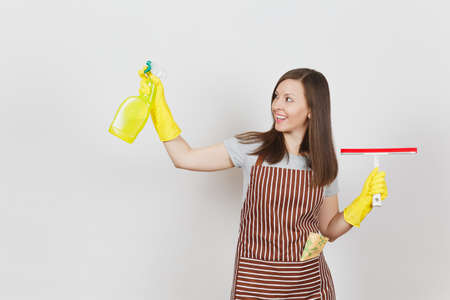 Young smiling housewife in yellow gloves, striped apron, cleaning rag in pocket isolated on white background. Housekeeper woman holding squeegee, spray bottle with cleaner liquid. Bottle copy space