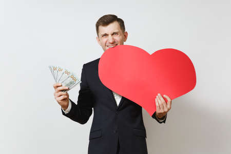 Dissatisfied man with big red heart, bundle of cash money dollars isolated on white background. Copy space for advertisement. St. Valentine's Day, International Women's Day, birthday holiday concept