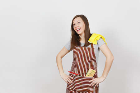 Young smiling housewife in striped apron with cleaning rag, squeegee, yellow gloves in pocket isolated on white background. Housekeeper woman standing with arms akimbo, looking up. For advertisement
