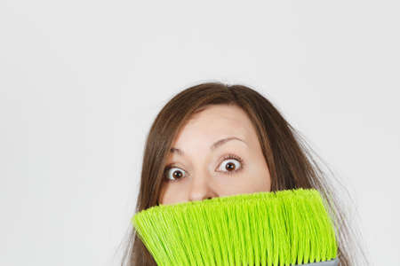 Close up of young fun crazy dizzy loony wild scared housewife with tousled hair isolated on white background. Mad housekeeper woman hiding behind green broom. Copy space for advertisement