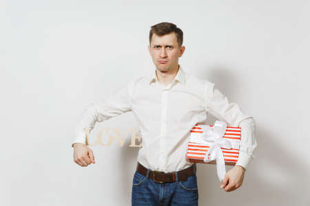 Young confused sad upset man in shirt holding armpit wooden word Love, present box with gift isolated on white background. St. Valentines Day, International Womens Day, birthday, holiday concept Stock Photo