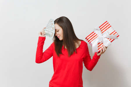 Woman holding bundle cash money dollars, red present box with gift isolated on white background. For advertisement. St Valentines Day, International Womens Day, Christmas, birthday, holiday concept