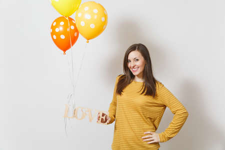 Beautiful romantic young smiling woman holding wooden word love, yellow orange air balloons on white background. Copy space for advertisement. St. Valentines Day or International Womens Day concept