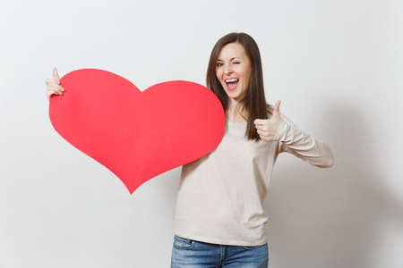 Beautiful young smiling woman holding big red heart, showing thumb up on white background. Copy space for advertisement. With place for text. St. Valentine's Day or International Women's Day concept