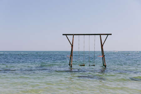 Beautiful sea landscape. High wooden swing decorated with colorful ribbons in a calm azure sea near the coastline. Banque d'images