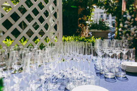 Preparing for party. Many clean shiny empty glasses for wine, champagne, whiskey, juice, water and other drinks on the table with a blue tablecloth in the gazebo at an outdoor party in the garden.
