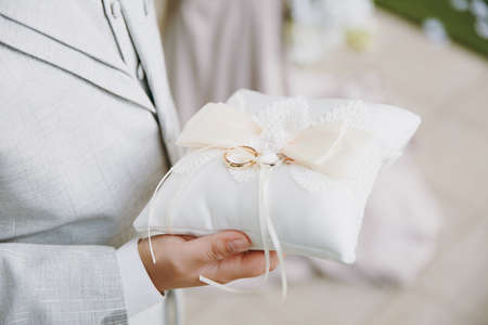 Close up Two beautiful stylish gold wedding rings of the bride and groom are on a refined white pillow with lace and bows in the hands of a man in a gray suit. Wedding accessories, jewelry.