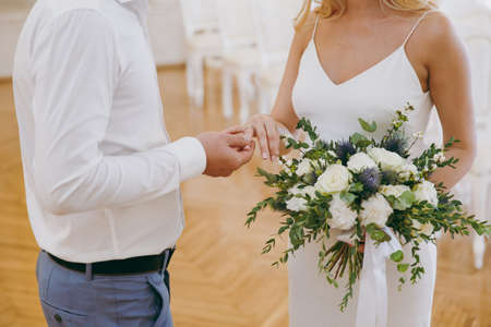 Beautiful wedding celebration. The groom in gray trousers and a white shirt puts engagement ring his pregnant blonde bride in simple white dress with a bouquet of light flowers and green twigs. Archivio Fotografico