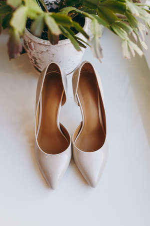 Close up Elegant light beige wedding varnish shoes with thin heels and sharp noses for the bride on a white gloss windowsill background. Wedding wear, accessories.