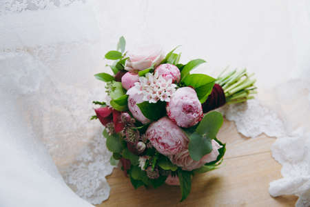 Close up A beautiful tender bridal bouquet in rose colors of roses, peonies and green twigs tied with a long velvet claret ribbon on a background of of white tulle. Wedding accessories for bride. Stock Photo
