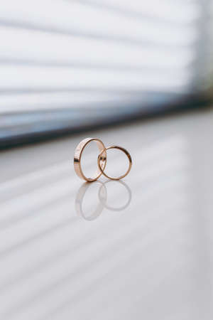 Close up Two beautiful stylish gold wedding rings of the bride and groom intersect on a white gloss windowsill background. Wedding accessories, jewelry.