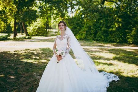 Beautiful wedding photosession. The bride in a white lace dress with a long plume, hairpin in hair, veil and bouquet of white and pink flowers in a large green garden on weathery sunny day.