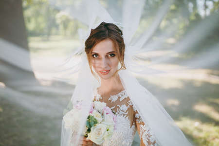 Beautiful wedding photosession. Portrait of the young smiling bride in a white lace dress and bouquet of white and pink flowers in a fluttering veil in a large green garden on weathery sunny day.