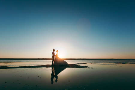 Beautiful wedding photosession. Silhouettes of the young bride and groom in a long lush dress on a coastline near the sea against a backdrop of a bright sunset in evening sunset.
