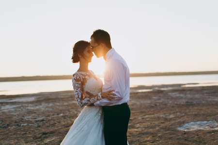 Beautiful wedding photosession. Handsome unshaved groom in a black trousers and young cute bride in white lace pattern dress with exquisite hairstyle on walk along the coastline near the sea sunset.
