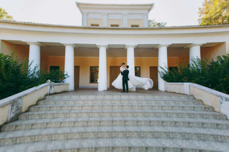 Beautiful wedding photosession. The groom in a black suit and glasses is circling in the arms his young cute bride in a white lace dress with a long plume at the top of the stairs of a large house.
