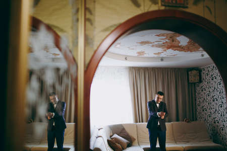 Morning preparation of the newlyweds for the wedding ceremony. The groom in white shirt, blue trousers, jacket and bow tie puts on cufflinks on sleeves in room with patterned wallpaper. Wedding wear.