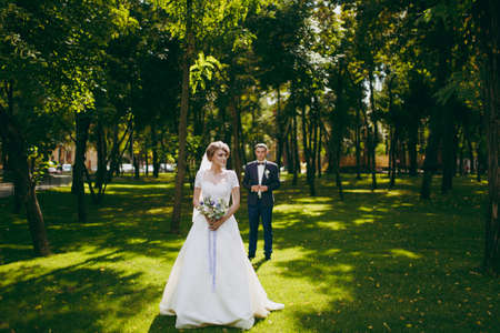 Beautiful wedding photosession. Handsome groom in blue formal suit and his elegant bride in white dress and veil with bouquet with beautiful hairdress on a walk in the big green park on a sunny day. Stock Photo