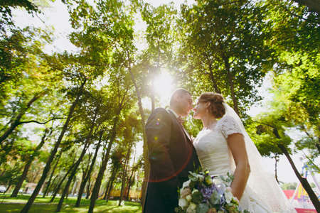 Beautiful wedding photosession. Handsome groom in blue formal suit with bouquet and his elegant bride in white dress and veil with beautiful hairdress on a walk in the big green park on a sunny day. Archivio Fotografico