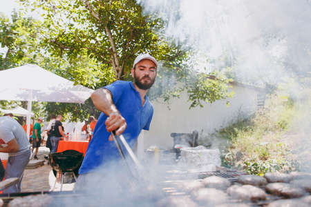 Odessa, Ukraine, 08-26-2017:A bearded tanned man in a blue T-shirt and cap prepares and turns over hot meat puffing steaks on grill with forceps at a barbeque party outdoors. Concept of lifestyle. Imagens - 100886077