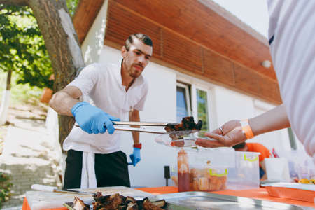 Odessa, Ukraine, 08-26-2017:A unshaved man in a white T-shirt at the dispensing table using forceps puts meat in a glass plate in hands of a man at a barbecue party outdoors. Concept of lifestyle. Sajtókép