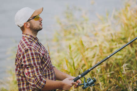 Side view Young unshaven man in checkered shirt, cap and sunglasses holds a fishing pole and unwinding reel on shore of lake near shrubs and reeds. Lifestyle, recreation, fisherman leisure concept Stock Photo