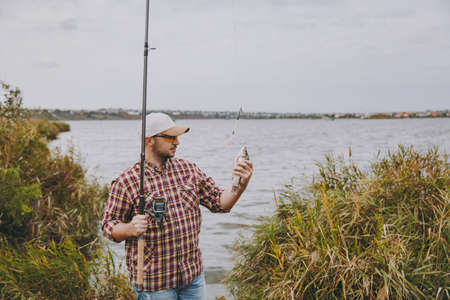 Young unshaven man in checkered shirt, cap and sunglasses pulled out a fishing pole and holds caught fish on shore of lake near shrubs and reeds. Lifestyle, recreation, leisure concept.