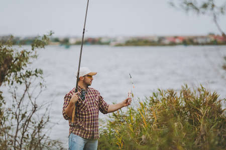 Side view Young unshaven man in checkered shirt, cap and sunglasses pulled out fishing pole and holds caught fish on shore of lake near shrubs and reeds. Lifestyle, recreation, leisure concept.