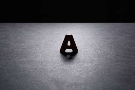 Wooden letter A on the dark texture with a black background with backlight. Lighting effect.