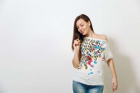 The beautiful European young smiling brown-haired woman with healthy clean skin, dressed in casual clothes standing with glasses for sight on a white background. Emotions concept.