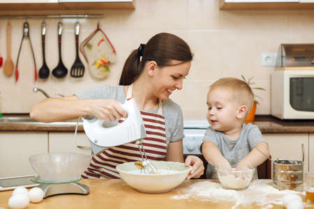 Little kid boy helps mother to cook Christmas ginger biscuit in light kitchen with tablet on the table. Happy family mom 30-35 years and child 2-3 in weekend morning at home. Relationship concept. Stock Photo