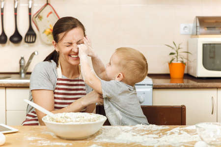 Little kid boy helps mother to cook Christmas ginger biscuit in light kitchen with tablet on the table. Happy family mom 30-35 years and child 2-3 have fun and throw flour home. Relationship concept