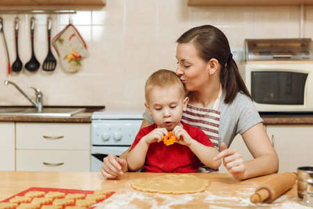 The little kid boy helps mother to cook Christmas ginger biscuit in light kitchen. Happy family mom 30-35 years and child 2-3 roll out dough and cut out cookies at home. Relationship and love concept
