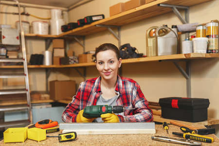 Beautiful caucasian young brown-hair woman in plaid shirt and gray T-shirt working in carpentry workshop at table place, drilling with drill holes in piece of iron and wood while making furniture