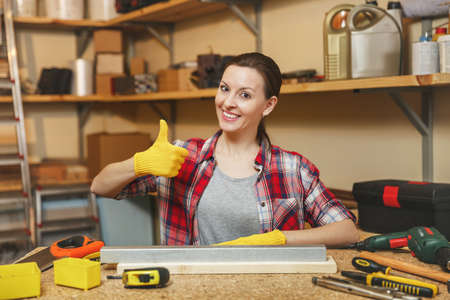 Beautiful smiling caucasian young brown-hair woman in plaid shirt, gray T-shirt, yellow gloves working in carpentry workshop at wooden table place with piece of iron and wood, different tools