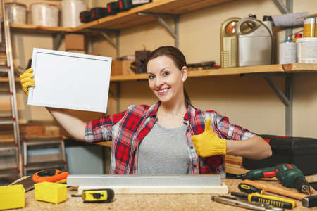Young woman in plaid shirt, gray T-shirt, yellow gloves working in carpentry workshop at wooden table place with blank frame, different tools. With empty place for text. Copy space for advertisement Stock Photo
