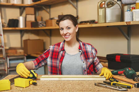 Beautiful caucasian young brown-hair woman in plaid shirt, gray T-shirt, yellow gloves working in carpentry workshop at wooden table place with different tools, measuring length of bar by tape Stock Photo