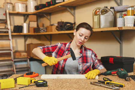 Pretty caucasian young brown-hair woman in plaid shirt, gray T-shirt, yellow gloves working in carpentry workshop at wooden table place with different tools, hammering nails into board with hammer Stock Photo