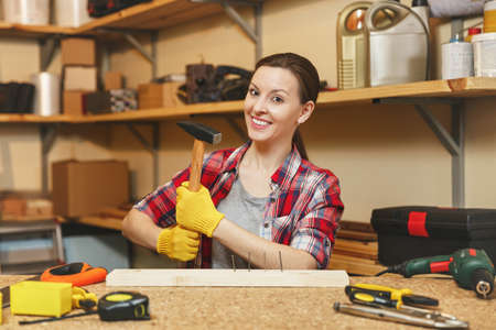 Beautiful caucasian young brown-hair woman in plaid shirt, gray T-shirt, yellow gloves working in carpentry workshop at wooden table place with piece of iron and wood, different tools. Hammering nail