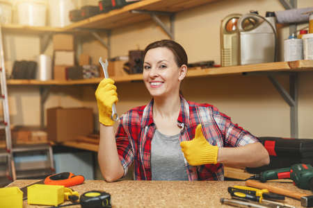 Beautiful smiling caucasian young brown-hair woman in plaid shirt, gray T-shirt, yellow gloves with spanner showing thumb up, working in carpentry workshop at wooden table place with different tools