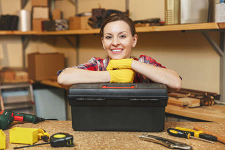 Beautiful smiling caucasian young brown-hair woman in plaid shirt, gray T-shirt, yellow gloves working in carpentry workshop at wooden table place with black toolbox, different tools. Gender equality