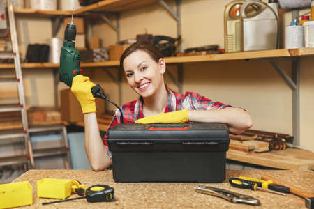 Beautiful smiling caucasian young brown-hair woman in plaid shirt, gray T-shirt, yellow gloves working in carpentry workshop at wooden table place, took power drill out of toolbox, different tools Stock Photo