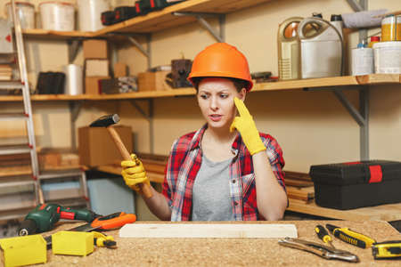 Pretty caucasian young brown-hair woman in plaid shirt, gray T-shirt, yellow gloves, protective helmet working in carpentry workshop at wooden table place with hammer, piece of wood, different tools