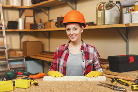 Beautiful caucasian young brown-hair woman in plaid shirt, gray T-shirt, yellow gloves, protective helmet working in carpentry workshop at wooden table place with piece of wood, different tools