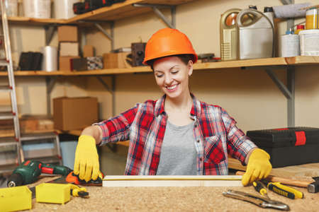 Young woman in plaid shirt, gray shirt, yellow gloves, protective helmet measuring length of piece of wood with tape measure, working in carpentry workshop at wooden table place with different tools Stock Photo