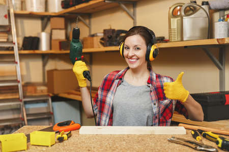 Beautiful caucasian young brown-hair woman in plaid shirt, noise insulated headphones working in carpentry workshop at table place, drilling with power drill holes in piece of wood, making furniture