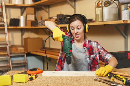 Angry stress upset young brown-hair woman in plaid shirt, noise insulated headphones working in carpentry workshop at table place, drilling with power drill holes in piece of wood, making furniture