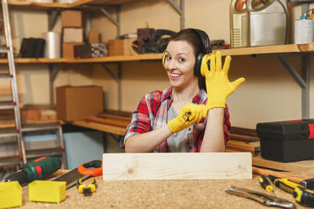 Pretty caucasian young brown-hair woman in plaid shirt, gray T-shirt, noise insulated headphones, yellow gloves working in carpentry workshop at wooden table place with piece of wood, different tools