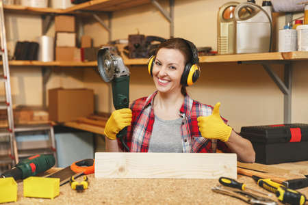Young woman in plaid shirt gray T-shirt noise insulated headphones yellow gloves working in carpentry workshop at wooden table place with different tools showing thumb up, sawing wood with power saw Stock Photo