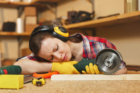 Young tired woman in plaid shirt, gray T-shirt, noise insulated headphones, yellow gloves working in carpentry workshop at wooden table place with different tools, sleeping on wood with power saw